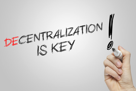 decentralization: Hand writing decentralization is key on grey background