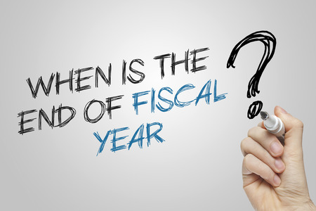 fiscal: Hand writing when is the end of fiscal year on grey background