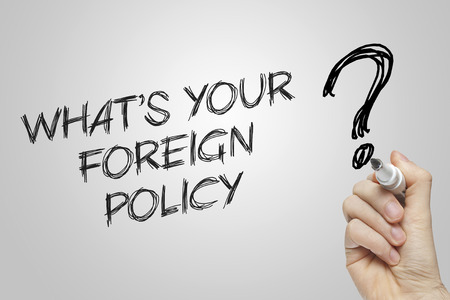 foreign policy: Hand writing what is your foreign policy on grey background Stock Photo