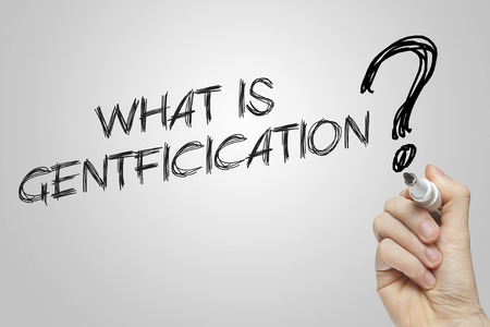gentrification: Hand writing what is gentrification on grey background Stock Photo