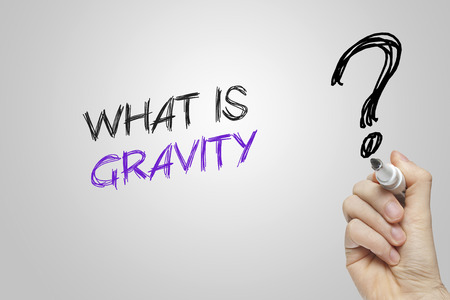 gravity: Hand writing what is gravity on grey background