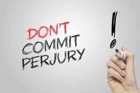 dishonesty: Hand writing dont commit perjury on grey background