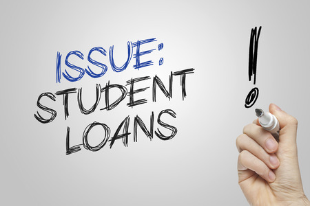 loans: Hand writing issue student loans on grey background Stock Photo