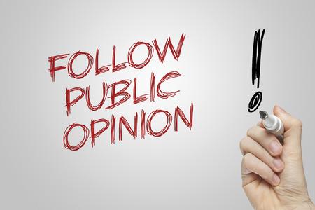 public opinion: Hand writing public opinion on grey background Stock Photo