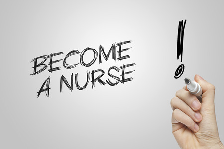 Hand writing become a nurse on grey background photo