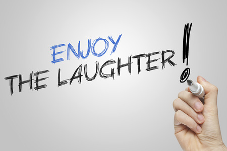 laughter: Hand writing enjoy the laughter on grey background
