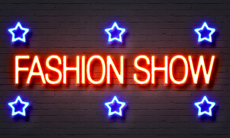 Fashion show neon sign on brick wall background Stock Photo