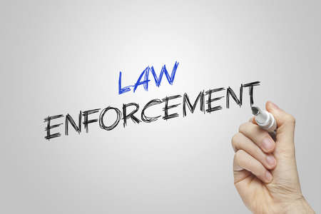 Hand writing law enforcement on grey background