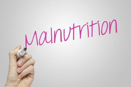 malnutrition: Hand writing malnutrition on grey background