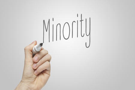 minority: Hand writing minority on grey background
