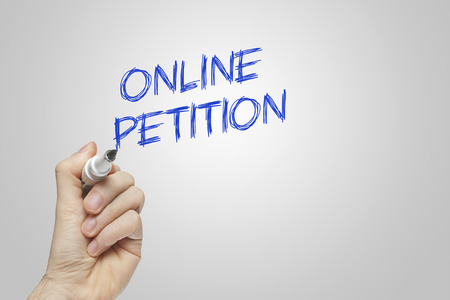 petition: Hand writing online petition on grey background Stock Photo
