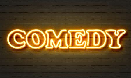 Comedy neon sign on brick wall background Stock Photo