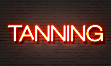 Tanning neon sign on brick wall background