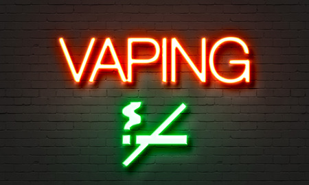 Vaping neon sign on brick wall background photo
