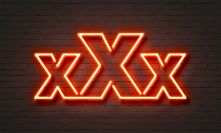 pornography: Xxx neon sign on brick wall background Stock Photo