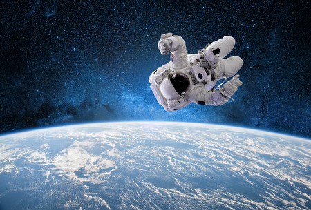 Astronaut in outer space with planet earth as backdrop. Elements of this image furnished by . Stock Photo