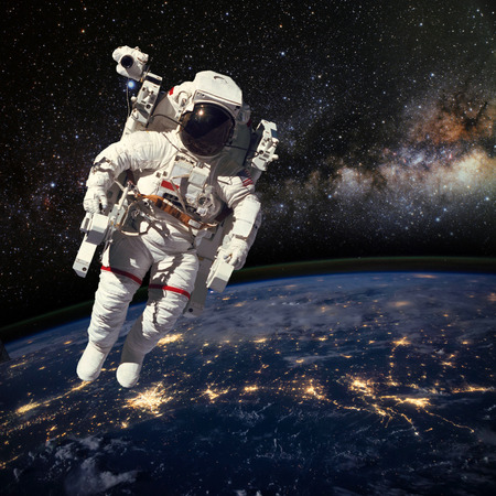 Astronaut in outer space above the earth during night time. Elements of this image furnished by .