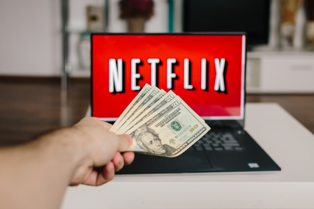 ZAGREB, CROATIA - DECEMBER 20, 2015: Netflix on laptop screen, man throwing US dollars at it. Netflix is an international provider of on-demand Internet streaming media.