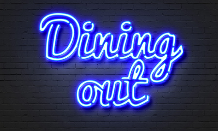 Dining out neon sign on brick wall background