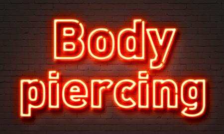pierce: Body piercing neon sign on brick wall background