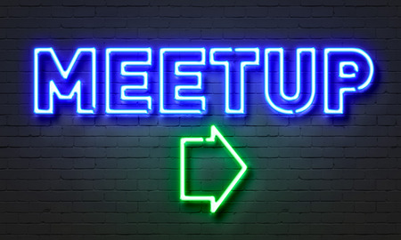 meetup: Meetup neon sign on brick wall background