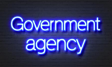 Het teken van het overheidsbureauneon op bakstenen muurachtergrond Stockfoto