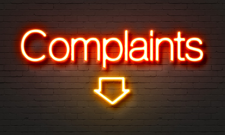 complaints: Complaints neon sign on brick wall background Stock Photo
