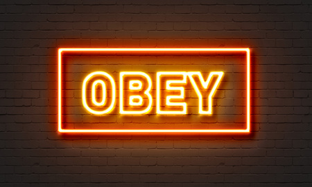 Obey neon sign on brick wall background Stock Photo