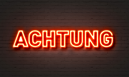 Achtung neon sign on brick wall background