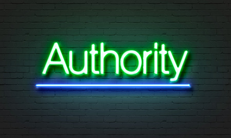 earned: Authority neon sign on brick wall background Stock Photo