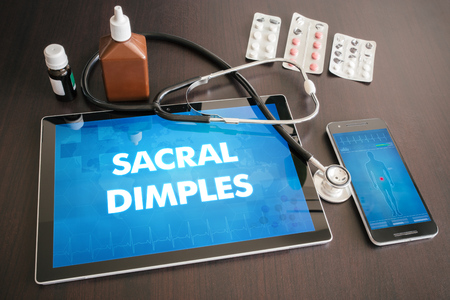sacral: Sacral dimples (congenital disorder) diagnosis medical concept on tablet screen with stethoscope.