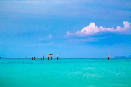 Pristine clean blue sea at Koh Lipe, Thailand at sunset with colorful pink clouds and distant wooden poles on the skyline in a travel and tourism concept