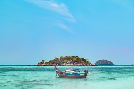 Traditional Thai wooden boat moored in a sheltered lagoon with crystal clear sparkling blue water with an offshore island in the background, Koh Lipe, Thailand Banque d'images - 130711175