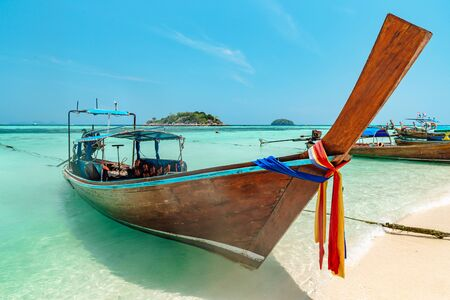 High wooden prow of a traditional Thai Boat decorated with a colorful cloth moored off an idyllic tranquil sandy beach with blue ocean in Koh Lipe, Thailand Banque d'images - 130711176