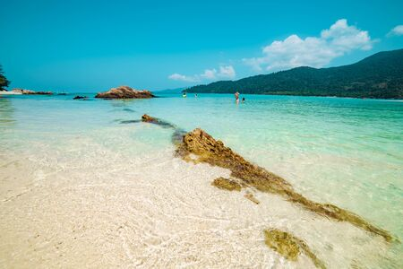 Crystal clear blue water off a beach in Koh Lipe, Thailand sparkling with reflections of sunlight in a sheltered lagoon or bay in a summer travel concept Фото со стока