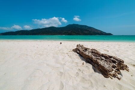Weathered driftwood log on a pristine sandy beach with view to a blue ocean and offshore island in Koh Lipe, Thailand in a travel concept