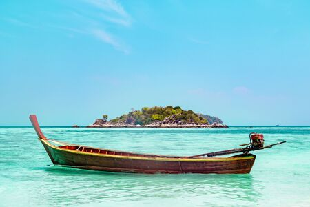 Traditional Thai wooden boat moored in a sheltered lagoon with crystal clear sparkling blue water with an offshore island in the background, Koh Lipe, Thailand Banque d'images - 130711181