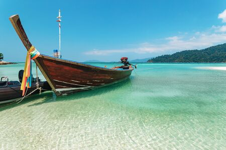 Traditional wooden Thai boat with colorful cloth tied round the prow moored in rippling sunlit water in a tranquil lagoon in Koh Lipe with copy space for summer travel Фото со стока