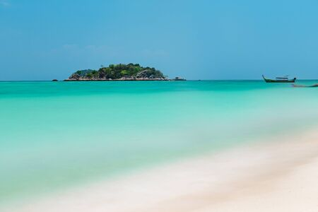Pristine tropical sandy beach in Koh Lipe, Thailand with a view over a blue ocean to a distant island and boat on a sunny summer day Фото со стока