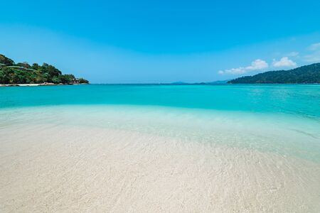 Azure blue tranquil ocean in a bay or lagoon with crystal clear water over white beach sand and distant headland with palm trees in Koh Lipe, Thailand in a travel concept