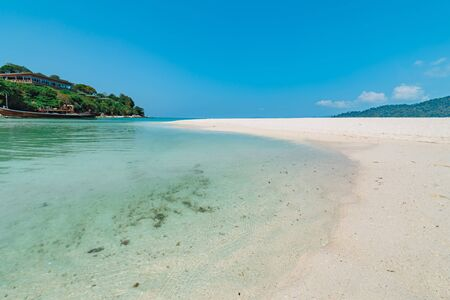 Pristine sandy beach and blue ocean, Koh Lipe, Thailand looking out over the water to an offshore island for an idyllic summer vacation Фото со стока
