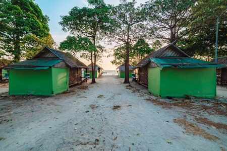 Cabana beach huts on a sandy beach Koh Lipe, Thailand with the glow of the rising sun behind leafy green trees in a scenic tropical landscape Фото со стока