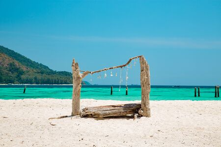 Wooden structure made with driftwood on a tropical sandy beach with turquoise blue ocean and island for an idyllic summer vacation in Koh Lipe, Thailand Banque d'images - 130712016