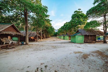 Beach cabanas under the trees at Koh Lipe, Thailand with recliner chairs and change facilities in a summer travel concept