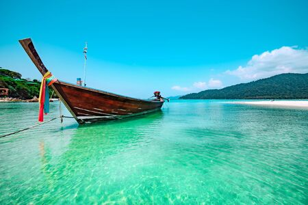 Traditional Thai boat moored in sparkling water with reflections of sunlight off a tropical beach in Koh Lipe, Thailand in a low angle view on a sunny summer day Banque d'images - 130712326
