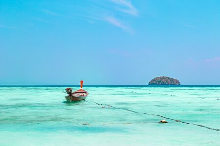Pristine tropical seascape with turquoise water and island on the horizon and a small traditional Thai boat moored in the shallow water at Koh Lipe, Thailand Stock Photo