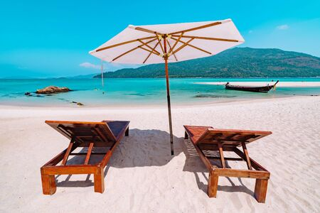 Two recliner chairs under a beach umbrella on a pristine sandy beach in Koh Lipe, Thailand overlooking a blue ocean with island in a travel concept