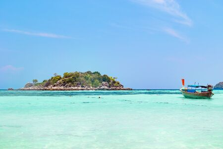 Tropical island with azure blue ocean and small traditional wooden Thai boat at Koh Lipe, Thailand in a travel concept