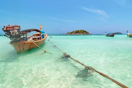 Long tail boat waiting for tourists in clear sky and white sand beach it a beautiful andaman sea with blue sky in a nice weather holiday at Koh Lipe, Sa-tun, Thailand