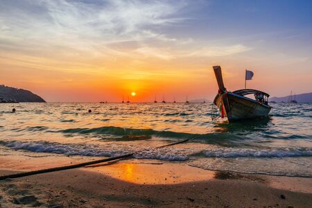 Dramatic orange sunset over a beach in Koh Lipe, Thailand with a traditional wooden Thai boat moored in the shallow surf and the colorful sky reflected in the water